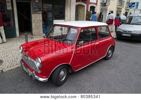 LISBON, PORTUGAL - MAY 28, 2014: A Classic Mini Cooper car parked in the street in Lisbon.  In 1999 the Mini was voted the second most influential car of the 20th century, behind the Ford Model T.