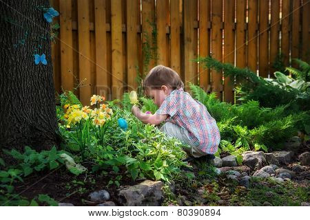 Little Boy Crouching Down Looking For Easter Eggs
