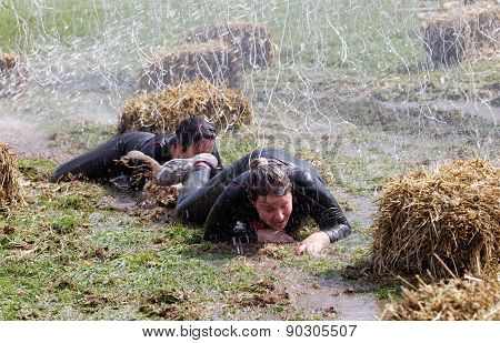 Two Woman Crawling In The Mud Between Sheaf Of Hay