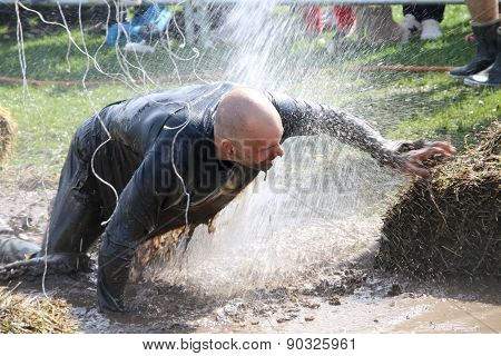 Man Fighting To Get Through The Mud, Squirted With Water, Electrified Wires Hanging