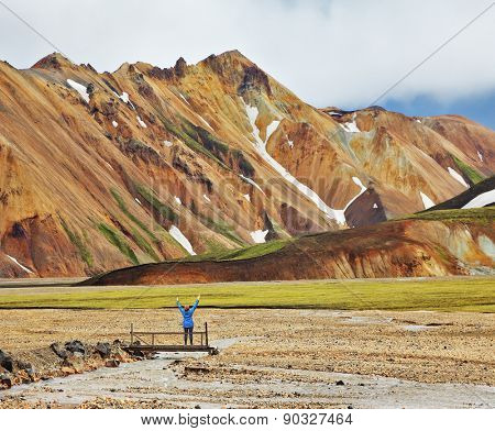 Pink and orange Mountains National Park Landmannalaugar in Iceland. Snow remained on the mountains last year. At the foot of the mountains is worth admiring woman -turist