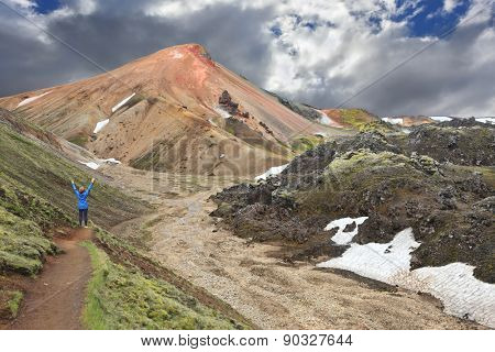The famous Valley Landmannalaugar. Delighted woman - tourist lifted her hands, unable to cope with emotions
