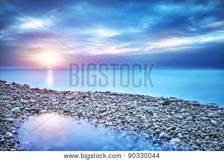 Beautiful seascape, amazing view of pebble coastline in mild sunset light, romantic evening on the beach, perfect place for summer holidays poster
