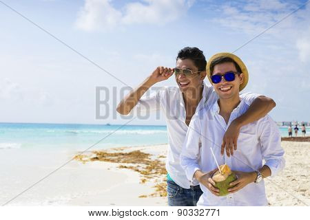 Gay couple drinking a coconut in the Caribbean