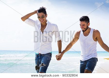 Couple of male friends running at the beach