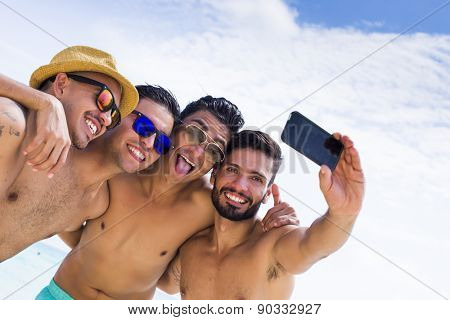 Group of four male friend taking a selfie at the beach