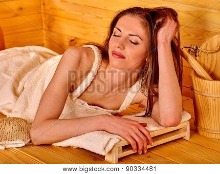 Young woman lying  at sauna. Overheating danger.
