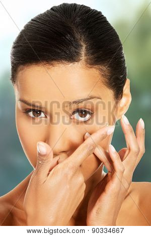 Woman applying contact lens in her eye. poster