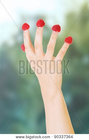 Cacuasian woman's hand with raspberries on fingers.