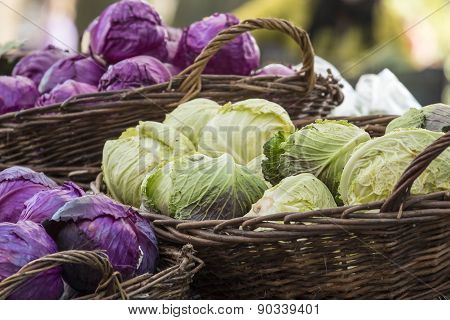 Fresh Organic Vegetables - Pile Of Green And Purple Cabbages In Baskets At Farmer's Market