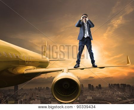business man and binoculars lens standing on plane wing spying acting use for commercial competition and top secret strategy poster