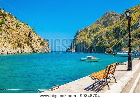 Bench, isthmus sea in port of Vathi Greek Island