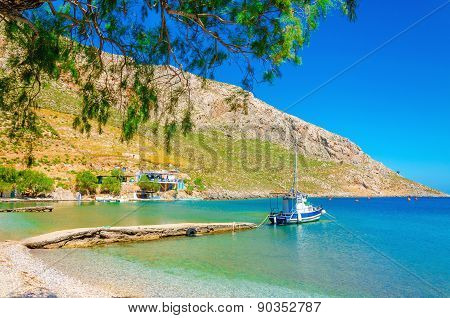 Small boat moored in peaceful bay with clear sand