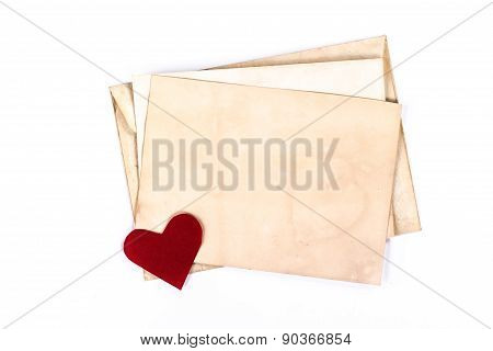 old yellow envelope with paper heart isolated on white background