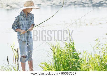 Angling Teenage Boy Looking At Handmade Green Twig Fishing Rod In His Arms