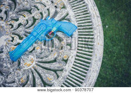 Blue Water Pistol On Table In Garden