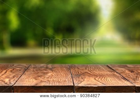 Empty wooden table with blurred city park on background, natural background with bokeh