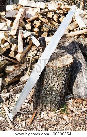 two-handled saw and ax in deck for chopping firewood pile of wood on rustic courtyard poster