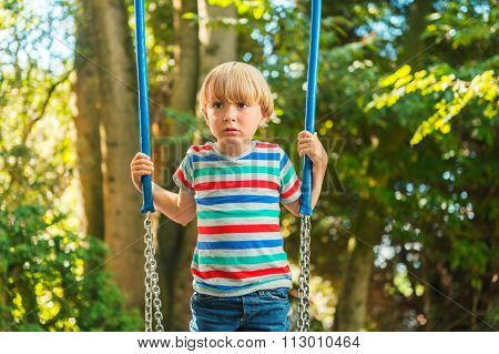 Cute young blond boy having fun on a swing on a nice summer day, wearing stipe tee