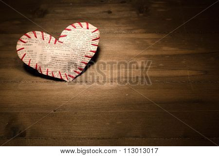 The Heart Sewed From A Newspaper Slice By Red Threads Lies On The Lit Site Of A Wooden Table.