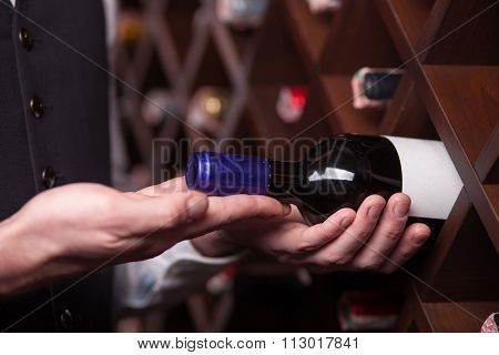 Experienced male worker is choosing drink in cellar