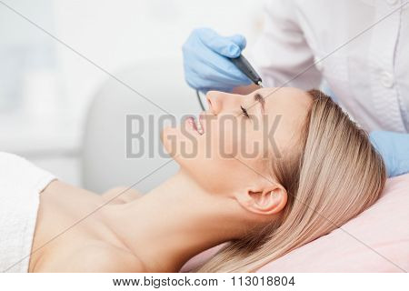 Close up of arms of experienced beautician performing laser skin treatment of skin on female face. The young woman is lying and smiling poster