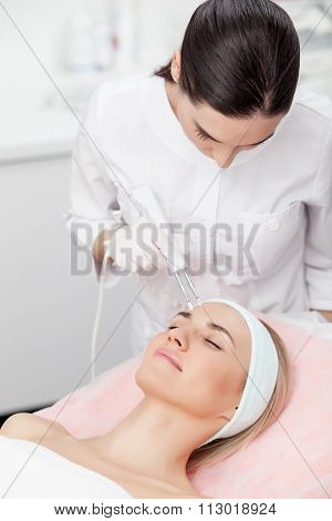 Professional young therapist is curing female skin