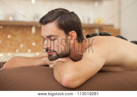 Attractive young guy is relaxing at beauty salon