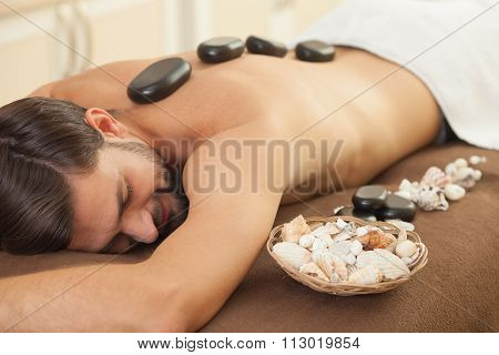 Attractive young guy is getting back massage