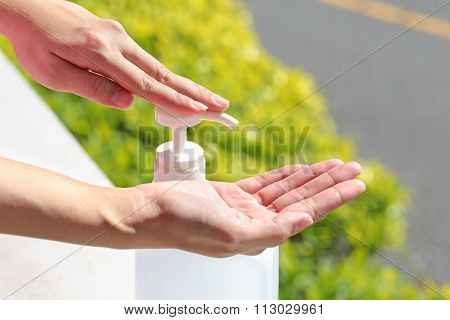 Female Using Gel Sanitizer With Green Healthy Blurry Background.