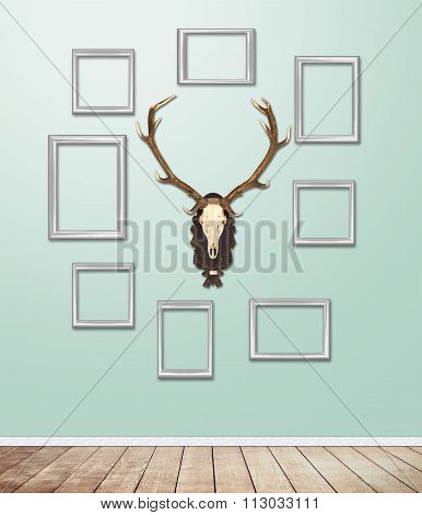 Silver Frame Decor With Antler Hang On Wallpaper With Light Flare.