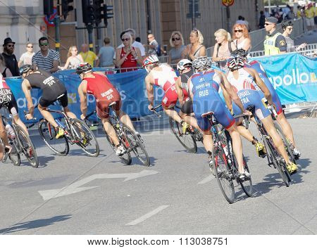 Rear View Of Large Group Of Male Cycling Triathlon Competitors