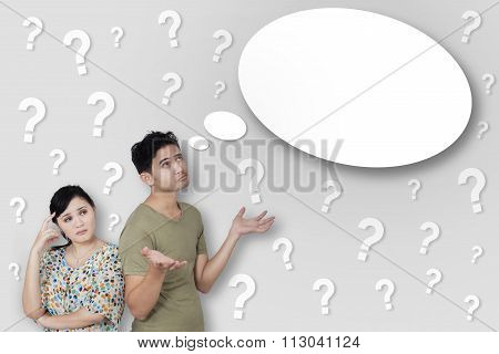 Thoughtful Couple with Many Question Marks