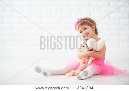 Little Child Girl Dreams Of Becoming  Ballerina With Ballet Shoes And Pointe Shoes