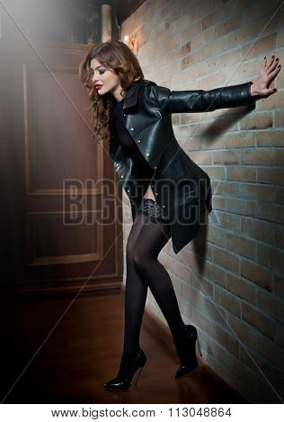Charming young brunette woman in leather coat over black stockings posing near red bricks wall
