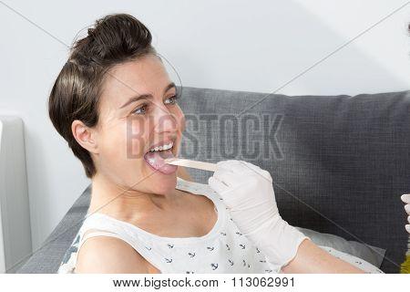 Nurse Putting Tongue Depressor Into Caucasian Pregnant Woman's Mouth.