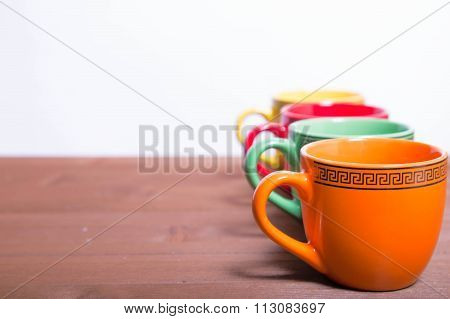 Multi-colored Ceramic Cups Stand On The Edge Of A Wooden Table