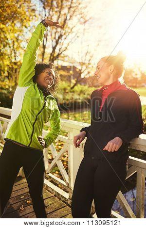 Two Smiling Sportswomen Stretching On Bridge