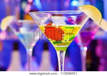 Casino chips in bar with alcohol glass and lime