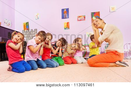 Kids in group play game pretending to sleep