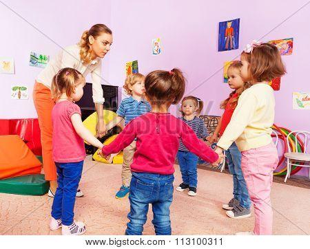 Teacher and group of kids in kindergarten