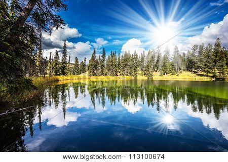 Jasper National Park in the Rocky Mountains of Canada. A great morning sun is reflected in smooth water of the lake. On shores of the lake grow coniferous forests