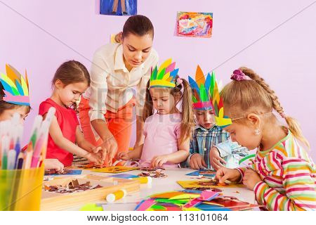 Teacher teach preschool kids in art class