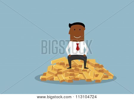 Wealthy and happy businessman sitting on gold bars