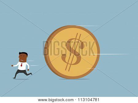 Businessman running away from huge golden coin