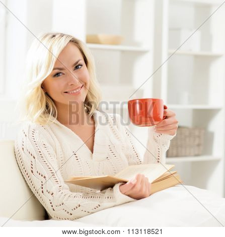 Beautiful smiling happy woman reading a book and having a cup of coffee in the morning.