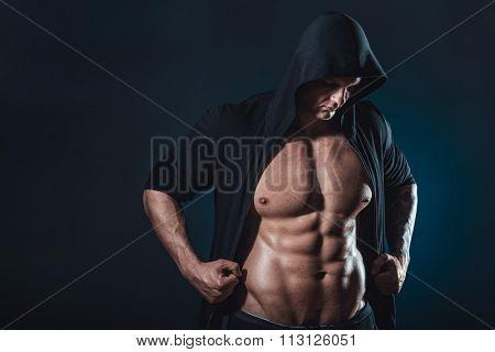 handsome muscular man posing in studio over black background