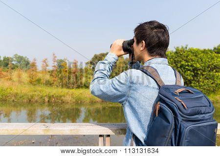 The back view of Man watching though binoculars
