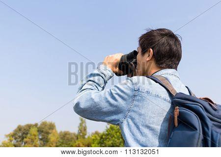 Man watching though binoculars