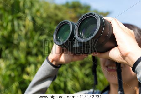 Young woman looking though binoculars at forest